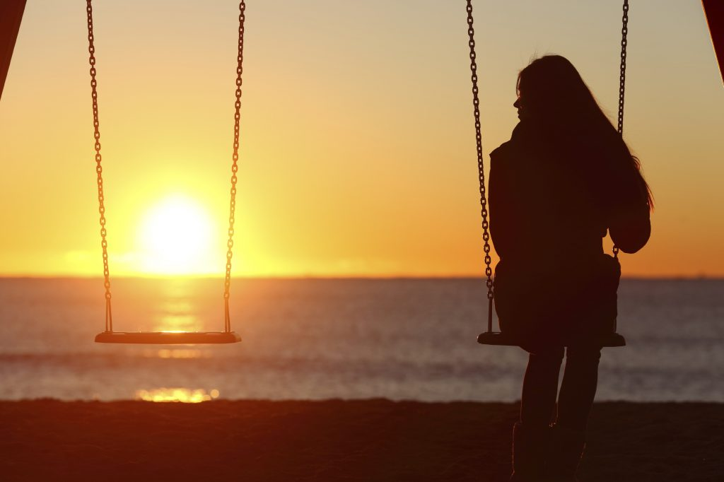 Single woman alone swinging on the beach and looking the other seat missing a friend